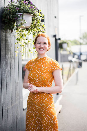 Meg Senior, wedding celebrant, in a bright yellow dress out in the Sheffield sunshine ready for a ceremony