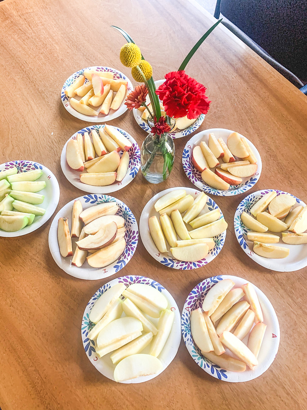 Ten plates with apple slices on them on top of a wooden table, a vase with red and yellow flowers in the middle of the table