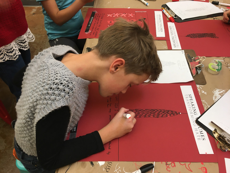 Helena elementary school student works on her own version of an exhibition poster for Speaking Volumes: Scores for Transforming Hate