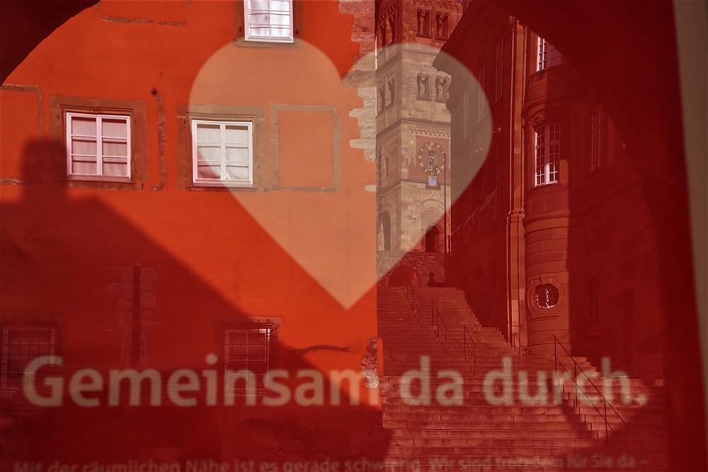 """In der Schaufenster Aufschrift """"gemeinsam da durch"""" spiegelt sich die Michaelskirche Schwäbisch Hall"""