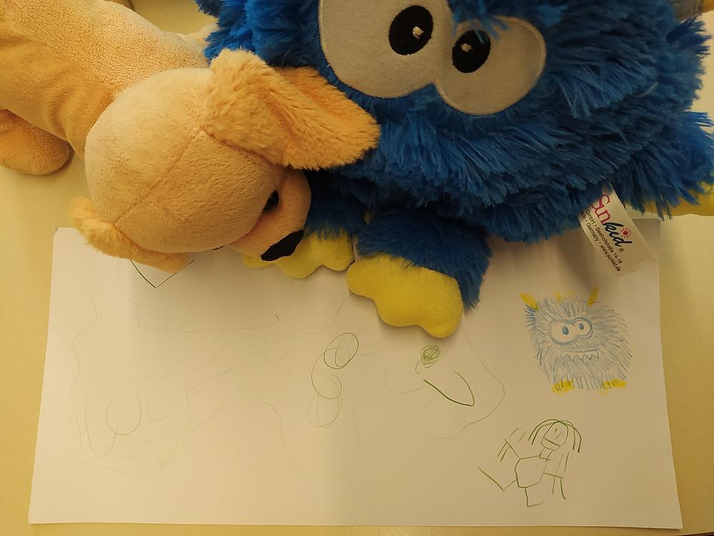 ein blaues, rundes Kuscheltier mit großen Augen sitzt mit einem Stofftier Hund auf einem Tisch. Vor ihnen liegt ein Blatt Papier auf dem ein Kind gemalt hat.