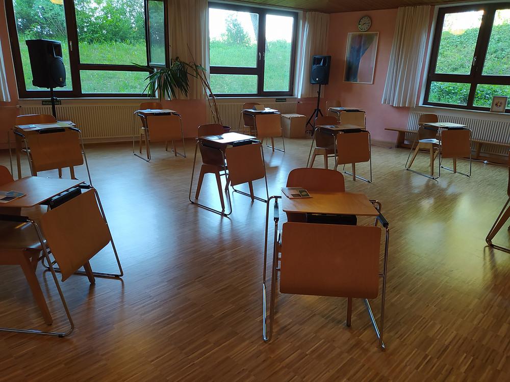 Es stehen Einzeltische mit Stühlen verteilt im Raum, um Abstand wahren zu können, ein Fenster ist zum Lüften geöffnet