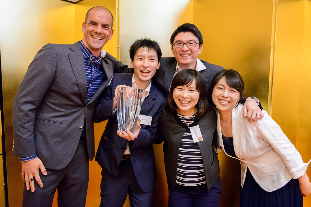 "JULY 2016 JMEC AWARDS  The A-Team By Thomas Beecher  On June 7 at the Tokyo American Club, months of rigorous preparation officially came to a close for participants in the 22nd annual Japan Market Expansion Competition (JMEC).  JMEC, which is backed by corporate sponsors and 18 foreign chambers of commerce—including the American Chamber of Commerce in Japan (ACCJ)—provides support and incentive for aspiring business innovators to produce real-life business plans for companies in or entering the Japanese market. This year's competition saw 58 participants across 12 teams plan and present their ideas to JMEC judges Rike Wootten, Debbie Howard, and Georg Loeer.  Tensions were high as JMEC chair Tom Whitson announced the winners to a packed house. ""How many of you have given up sleep?"" Whitson quipped, referring to the grueling seven-month process, which includes lectures, mentoring, and five months spent preparing a business plan on topics typically not familiar to participants.  The Journal spoke to Cory McGowan and Satoshi Ohashi, members of ""Team A,"" which won first prize with a potential new venture project for Fusion Systems, as well as Whitson and program director Trond Varlid.  https://journal.accj.or.jp/the-a-team/  The ACCJ - 在日米国商工会議所 http://www.accj.or.jp   JMEC - Japan Market Expansion Competition http://www.jmec.gr.jp/"