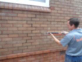 Buildfix technician repairing external cracked wall