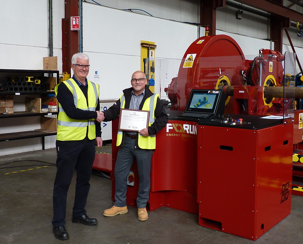 David Neill of TAM International (left) receives a plaque from George Hendry, business development manager for Forum AMC, recognising the purchase of the 350th RT torque machine.