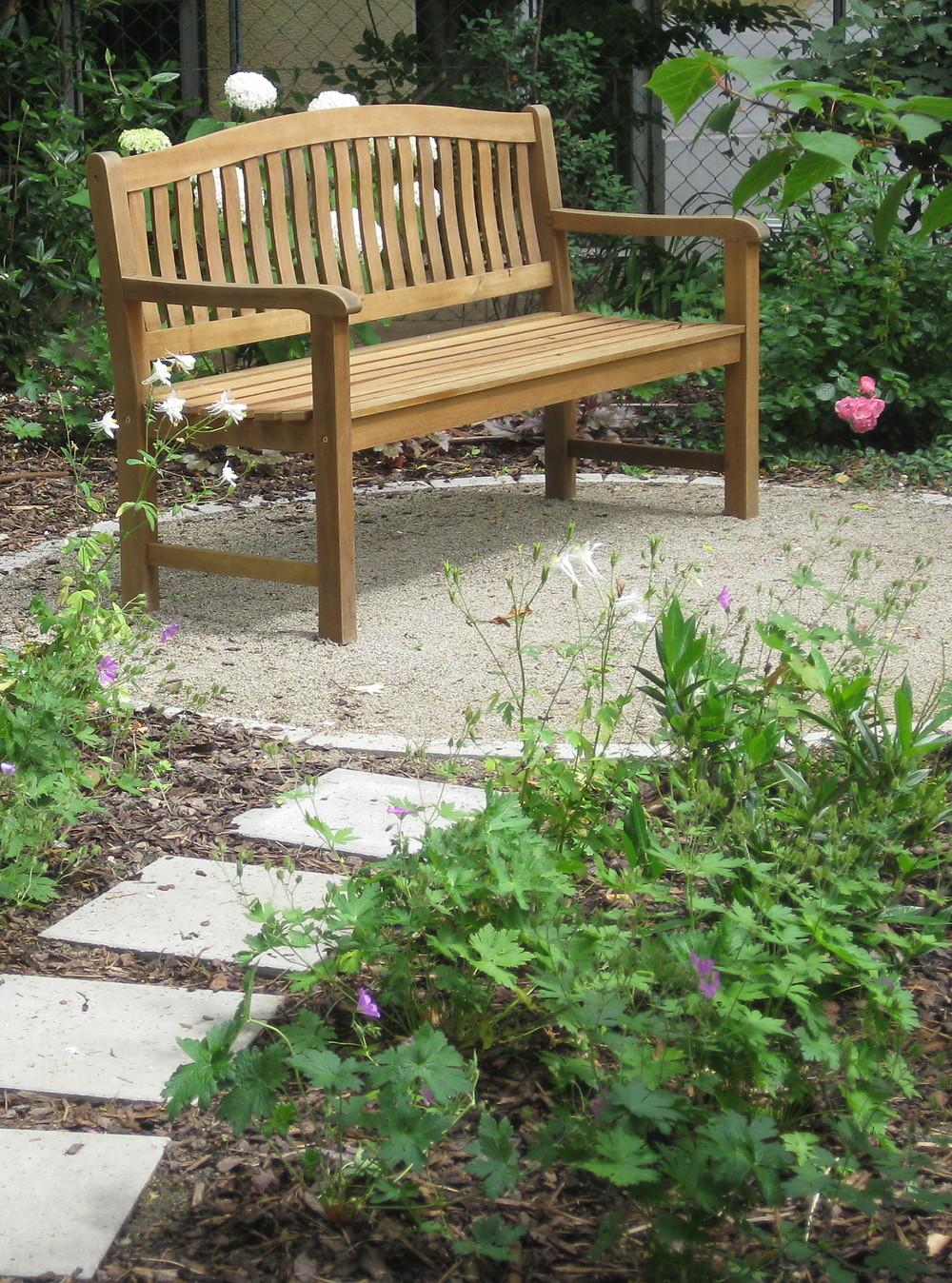 garden bench,roses, geraniums, compacted gravel, circular patio,