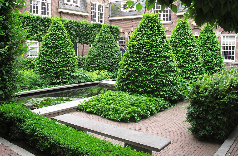 Topiary garden, pleached trees, canal water feature, floating stepping stone, flemmish brick, stone bench, traditional garden,