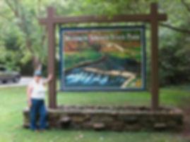 Arlene standing at entrance sign