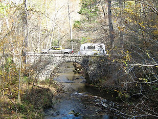Truck pulling camper over bridge at Blanchard Spings