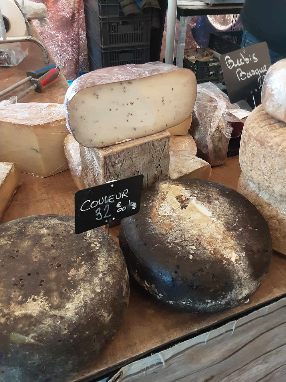 Large French cheese rounds and half rounds stacked on a stall's counter