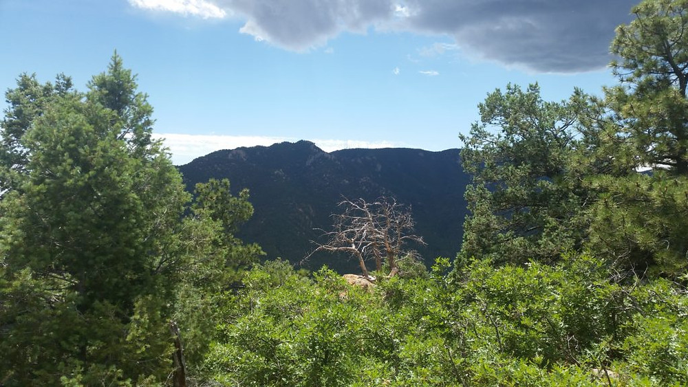 The view towards Cheyenne Mountain (south) from the summit of Muscoco. The sun came out at the perfect moment! If you zoom in, you can see the antenna farm at the top of the mountains in the distance.