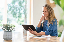 smiling-woman-at-home-sitting-at-table-and-looking-at-tablet-SBOF03734.jpg