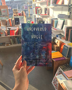 a hand holding the Uncovered Voices anthology