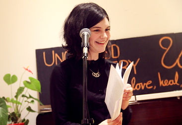 a woman reads a poem at a poetry reading