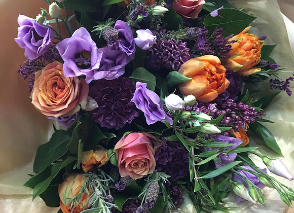 Purple and orange flowers in bouquet. including tulips and Lizianthus