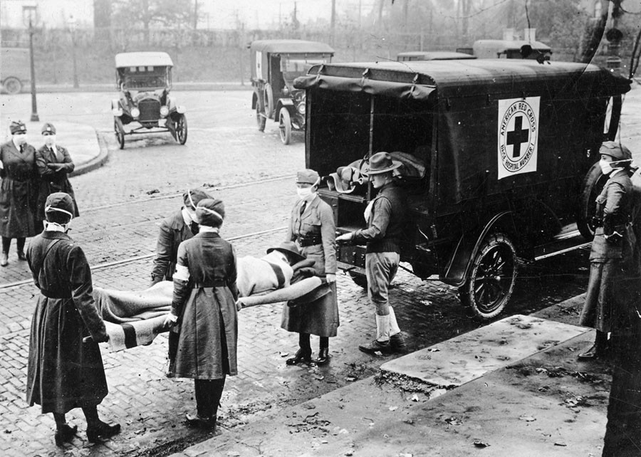 With masks over their faces, members of the American Red Cross remove a victim of the Spanish Flu from a house at Etzel and Page Avenues, St. Louis, Missouri, 1918. St. Louis Post Dispatch