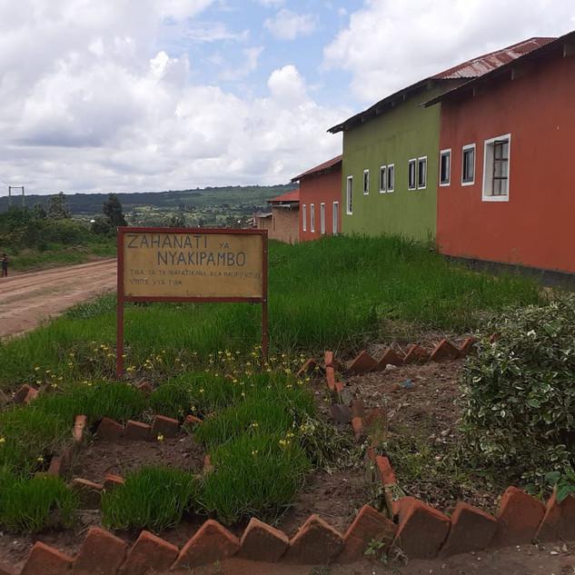 L'edificio del Dispensario di Nyakipambo. Il cartello recita: Dispensario di Nyakipambo. Il trattamento per la TB è disponibile gratuitamente in tutti i centri di cura.