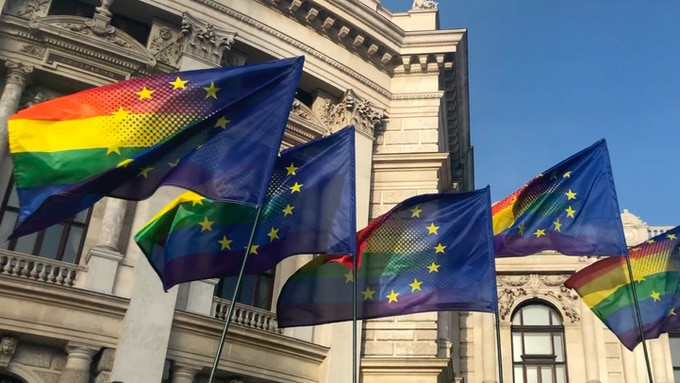 Four flags displaying the pride rainbow and the blue and yellow stars of the European Union