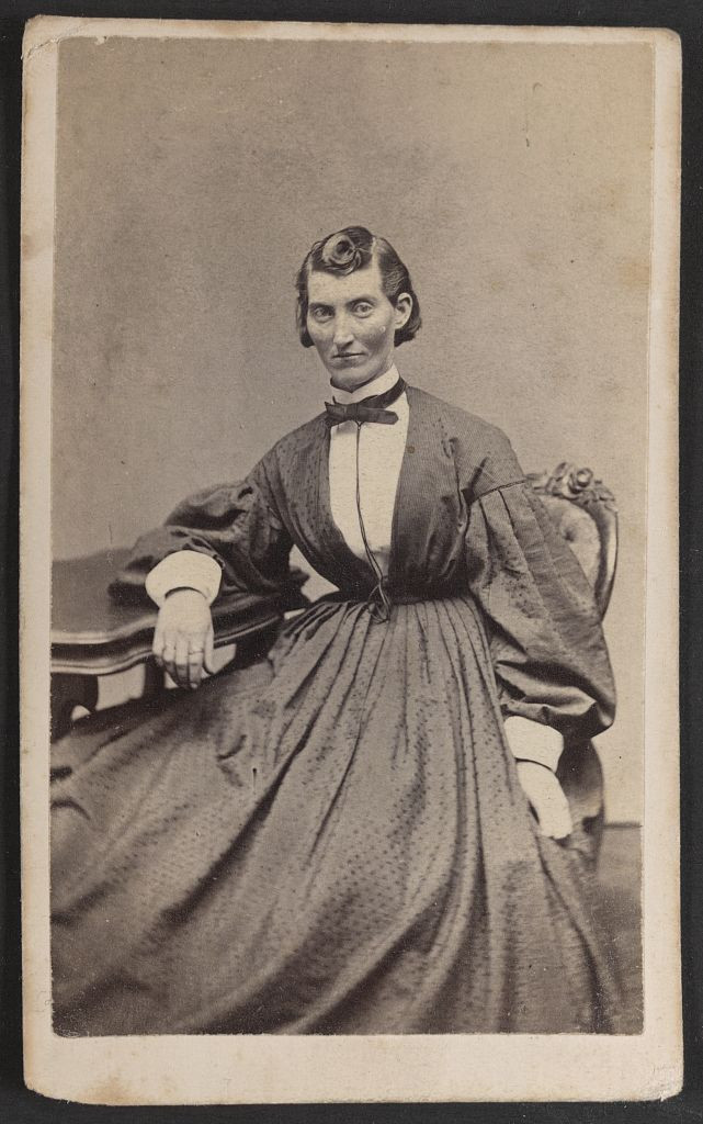 An image of a woman in a long dress leaning on a desk in black and white