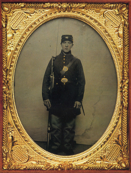 Lyons Wakeman dressed in his civil war uniform, holding a rifle. The image is bordered with a gold frame.