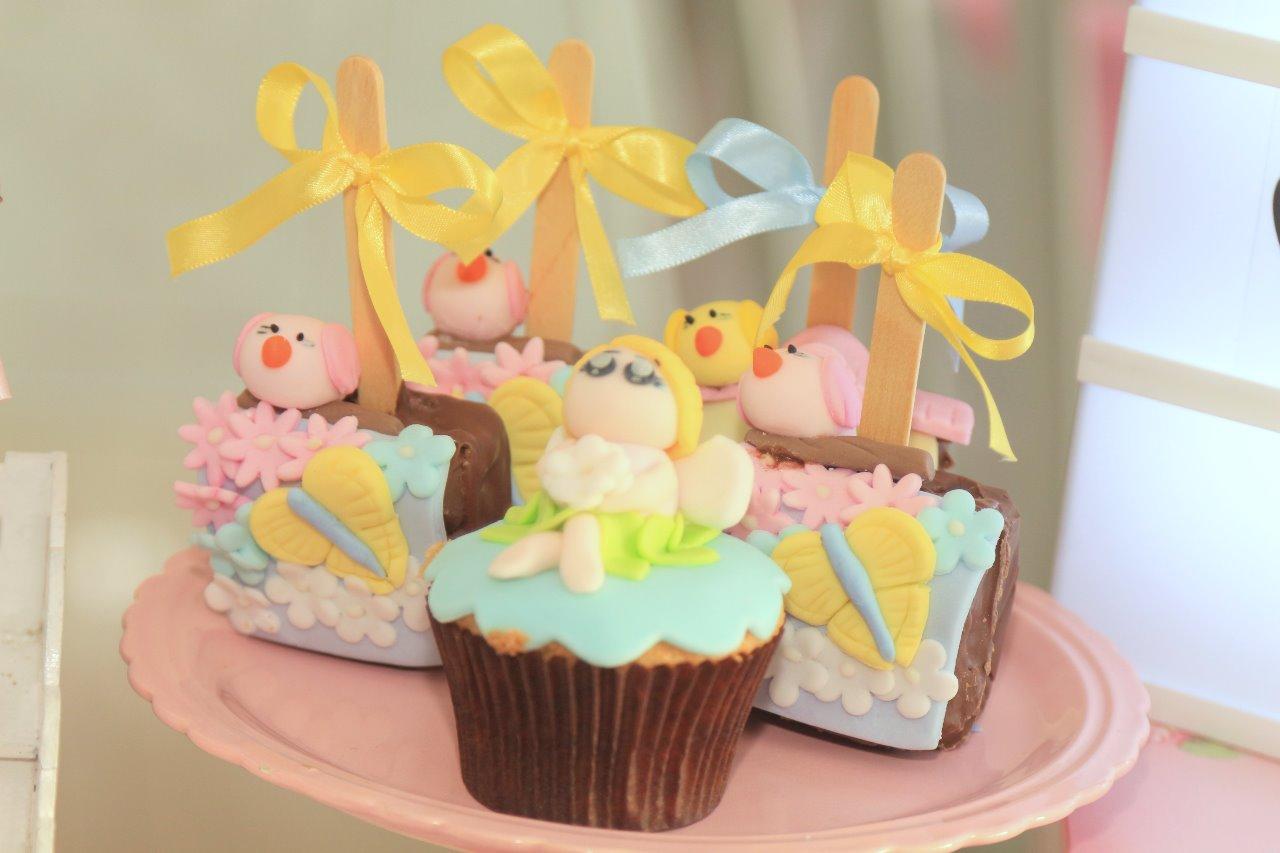 Pães de mel no palito e cupcake.