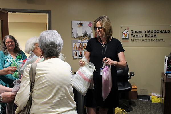 Jenny Bosking, of Ronald McDonald Room accepts baby blankets from Westminster Presbyterian Church.