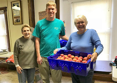 Volunteers at Loaves and Fishes accept a donation of apples.