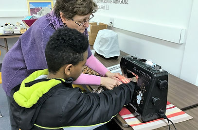 Westminster Sunday School Coordinator, Val Neubauer, helps Abdisa Ali sew a bag as part of a mission project.