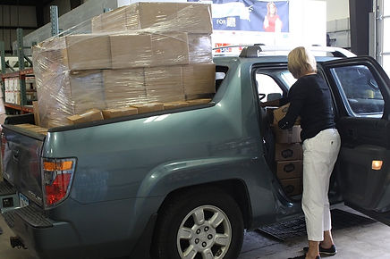 Ruth Quisling loads up a truck of boxes of food for Loaves & Fishes Food Pantry.