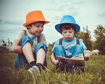 kids-sitting-on-green-grass-field-109407