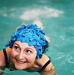 Older woman in a blue, floral swim cap swims in a pool with a smile