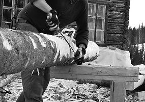 En av studentene i bygningsvern barker tømmer til restaurering
