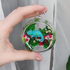 Chamäleon umgeben von Dschungelpflanzen / Glas Kugel