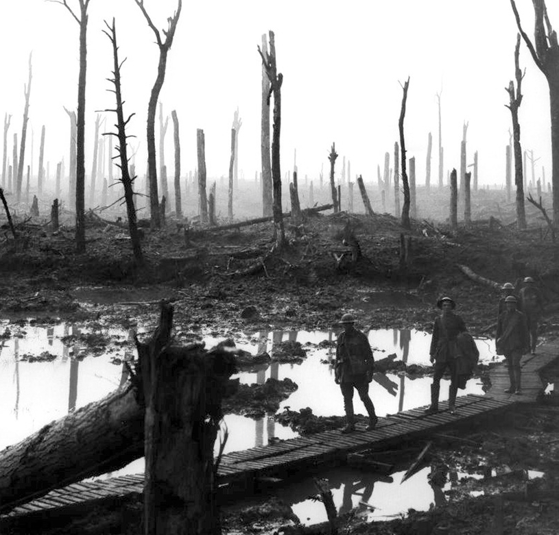Soldiers of an Australian 4th Division field artillery brigade walking through the devastated landscape on a duckboard track.