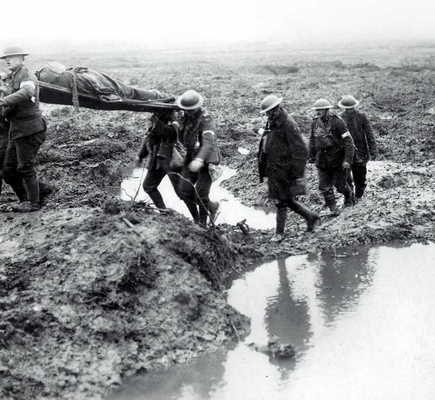 Stretcher-bearers carry wounded Canadians towards an aid post during the Battle of Passchendaele.