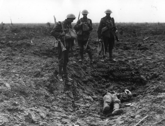 Three British guardsmen looking at the body of a dead German in a shell hole on July 31, 1917.
