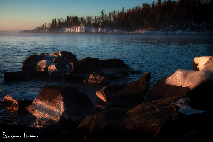from the sun splashed rocks in front of me, i watched as the bluffs encased in ice across the way also started to absorb the sun's inviting tones. you can see a bit of wispy sea smoke toward the left outermost point of the land.