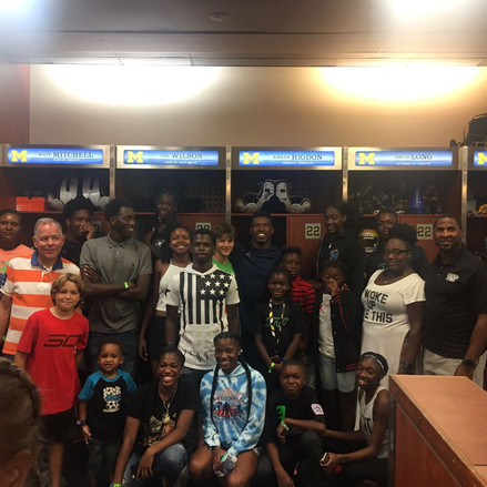 OJS CEO Sheldon Cantrell in University of Michigan football locker room with students.