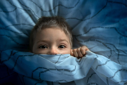 boy in bed with his eyes open. the child
