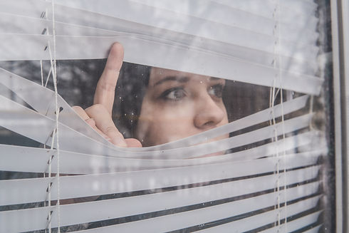 Woman Looking Through the Blinds. Girl l