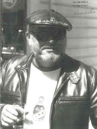 willie in leather jacket with drink in h