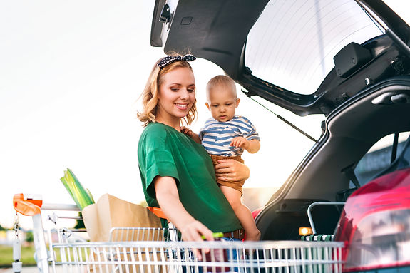 Mother with baby boy putting shopping in