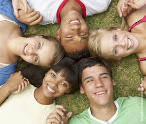 A group of young people smile and hold hands while lying in the grass.