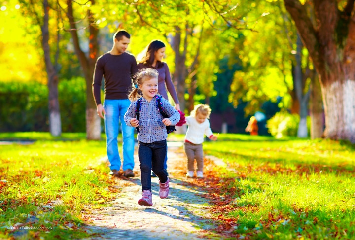 A family walks through the park on a sunny autumn day.