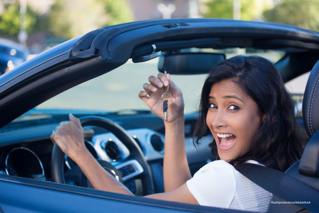 A happy young woman sits in her new car holding up the car keys.