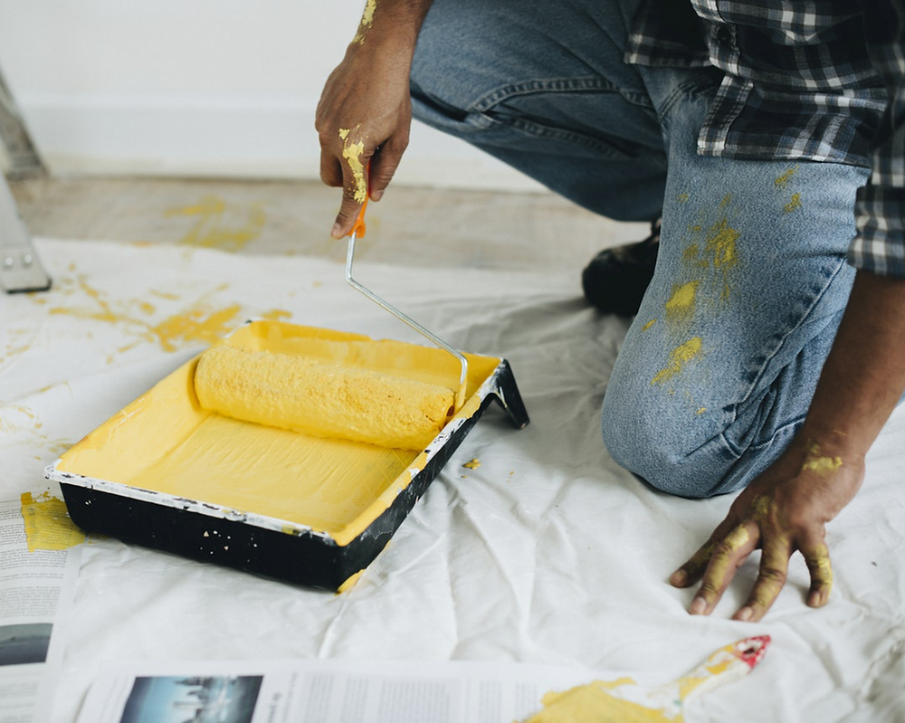 A man paints a room in yellow paint.