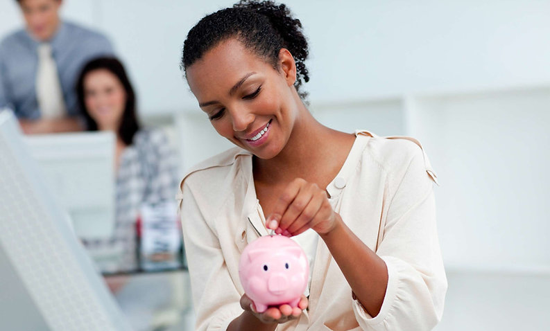 Savings Accounts. A woman drops a coin ntoa piggy bank.