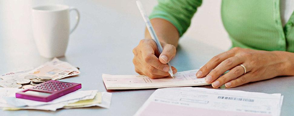 Checking Accounts. A woman writes a check.