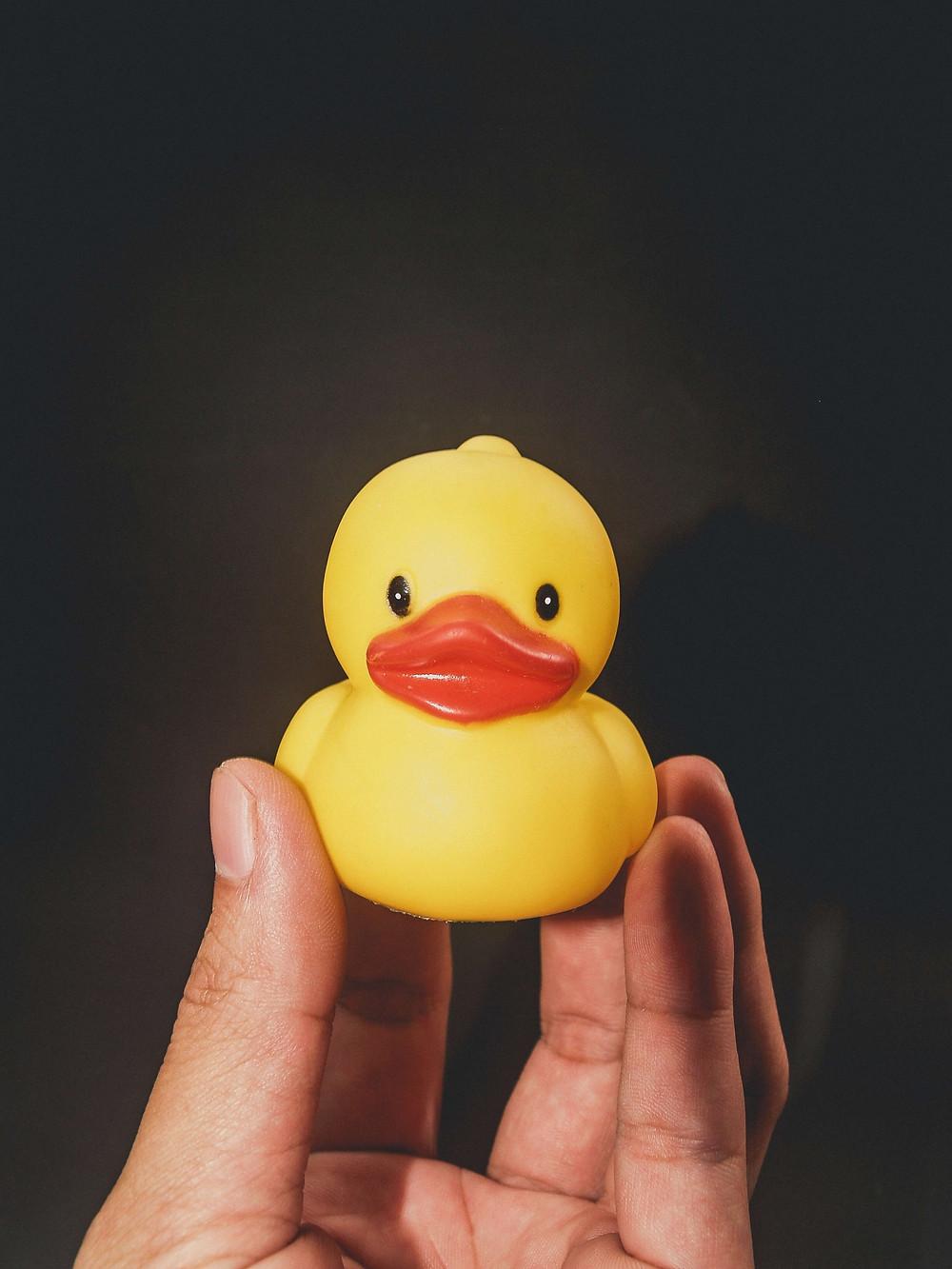 Uma mão segura um pato de plástico amarelo