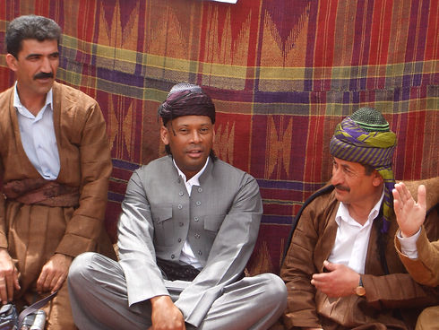 Mike Russell sitting with Iraqi-Kurds in traditional clothing